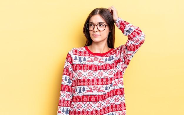 若いヒスパニック系の女性は、頭をかいて、戸惑い、混乱していると感じています。 chistmasと新年のコンセプト