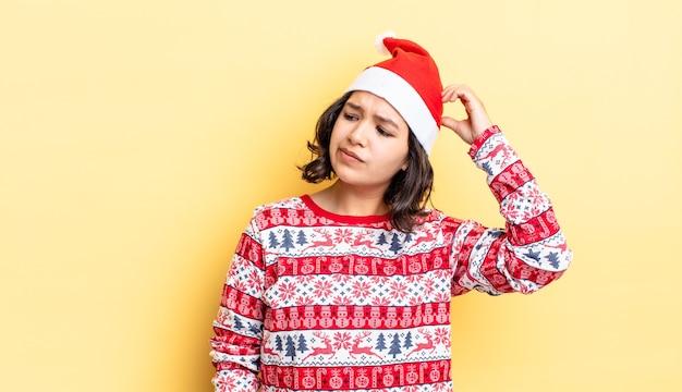 若いヒスパニック系の女性は、頭をかいて、戸惑い、混乱していると感じています。クリスマスのコンセプト