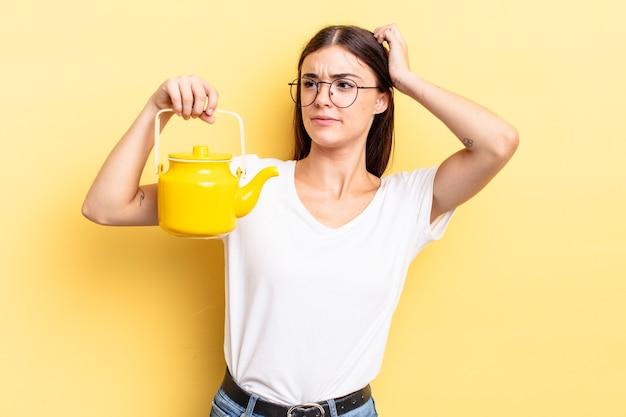 Молодая латиноамериканская женщина чувствует себя озадаченной и сбитой с толку, почесывая голову. концепция чайника