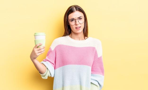 困惑と混乱を感じている若いヒスパニック系女性。コーヒーのコンセプトを奪う