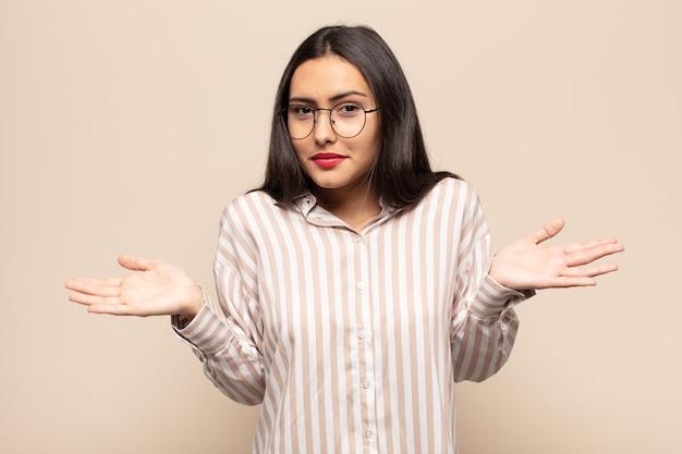Молодая латиноамериканка чувствует себя озадаченной и сбитой с толку, неуверенной в правильном ответе или решении, пытается сделать выбор