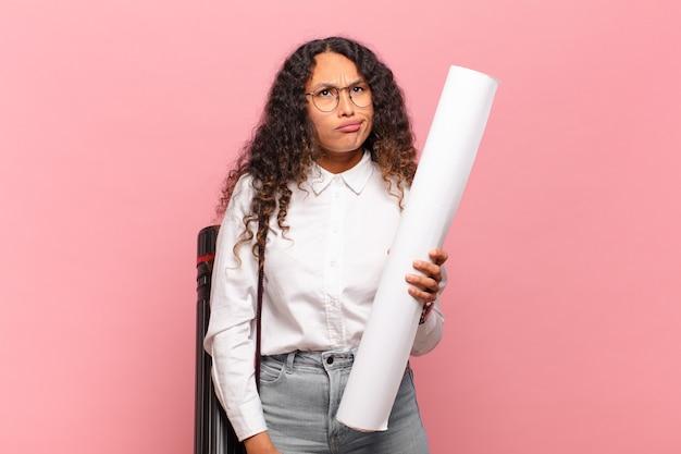 ヒスパニック系の若い女性は、戸惑い、混乱し、予期せぬ何かを見ている愚かな、唖然とした表情をしています。建築家の概念