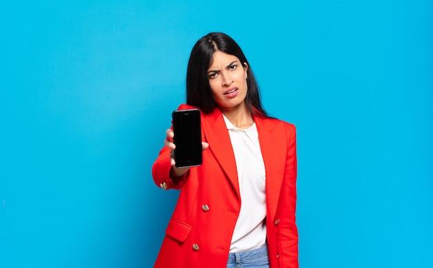 Молодая латиноамериканка, растерянная и озадаченная, с тупым, ошеломленным выражением лица смотрит на что-то неожиданное. пространство для копирования экрана телефона