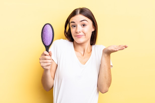 Young hispanic woman feeling puzzled and confused and doubting. hair brush concept