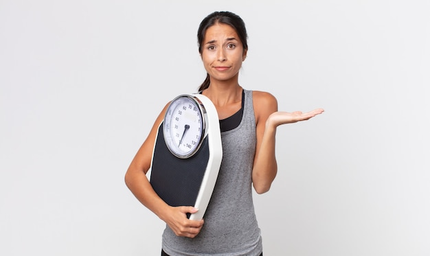 Young hispanic woman feeling puzzled and confused and doubting and holding a weight scale. diet concept