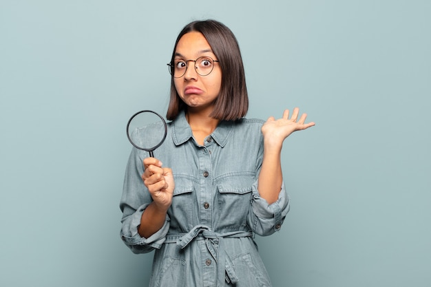 Young hispanic woman feeling puzzled and confused, doubting, weighting or choosing different options with funny expression