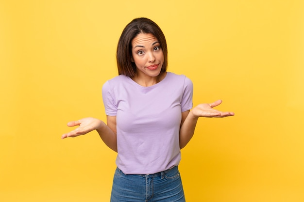 Young hispanic woman feeling puzzled and confused and doubting