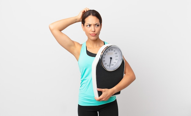 Young hispanic woman feeling puzzled and confused, scratching head and holding a scale