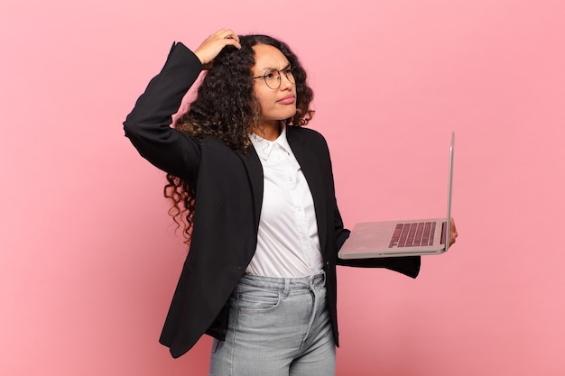 Young hispanic woman feeling puzzled and confused, scratching head and looking to the side. laptop concept
