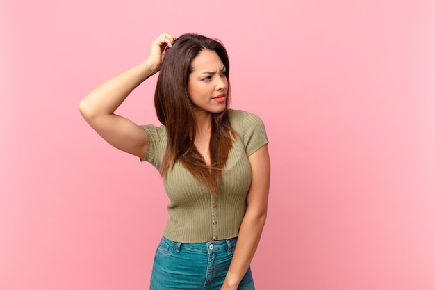 Young hispanic woman feeling puzzled and confused, scratching head
