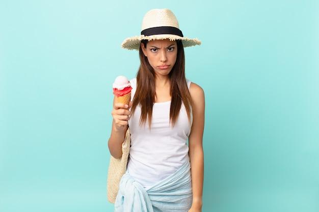 若いヒスパニック系の女性は、不幸な表情で悲しみと泣き言を感じ、泣いてアイスクリームを持っています。シュメールの概念