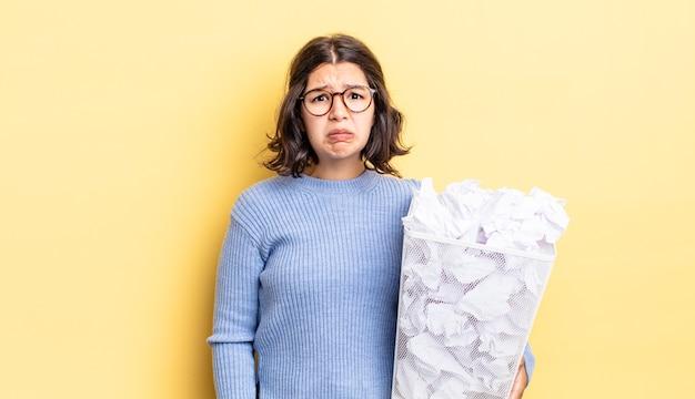 不幸な表情で悲しみと泣き言を感じ、泣いている若いヒスパニック系女性はゴミ箱の概念に失敗します