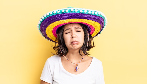 젊은 히스패닉계 여성이 불행한 표정을 지으며 울고 있습니다. 멕시코 모자 개념