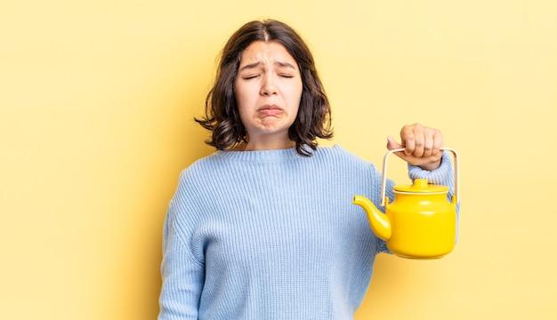Молодая латиноамериканская женщина грустит и плаксивает с несчастным взглядом и плачет. концепция чайника