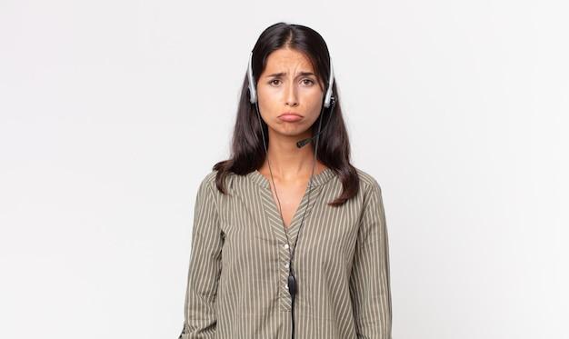 젊은 히스패닉계 여성이 불행한 표정으로 슬퍼하고 헤드셋을 끼고 울고 있습니다. 텔레마케팅 개념