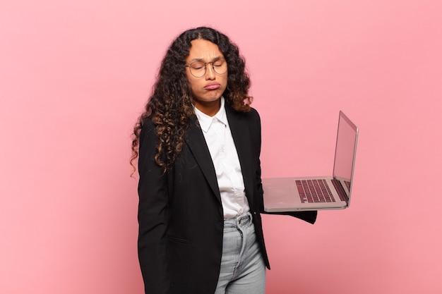 若いヒスパニック系の女性は、悲しくて悲しげな表情で泣き叫び、否定的で欲求不満な態度で泣いています。ラップトップのコンセプト