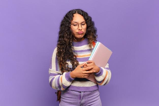 若いヒスパニック女性は、悲しげな表情で悲鳴を上げ、否定的で欲求不満な態度で泣いている