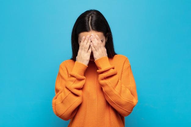 젊은 히스패닉 여성은 슬프고, 좌절하고, 긴장하고, 우울하고, 두 손으로 얼굴을 가리고, 울고 있다
