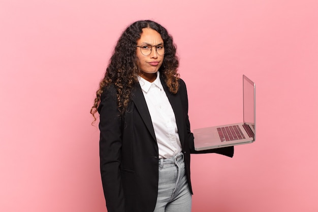 Young hispanic woman feeling sad, upset or angry and looking to the side with a negative attitude, frowning in disagreement. laptop concept