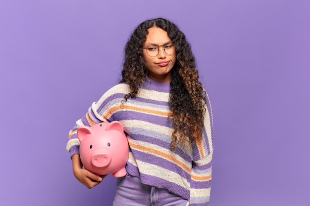 Young hispanic woman feeling sad, upset or angry and looking to the side with a negative attitude, frowning in disagreement. piggy bank concept