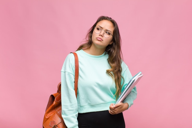 Young hispanic woman feeling sad, upset or angry and looking to the side with a negative attitude, frowning in disagreement