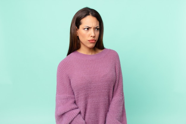 Young hispanic woman feeling sad, upset or angry and looking to the side