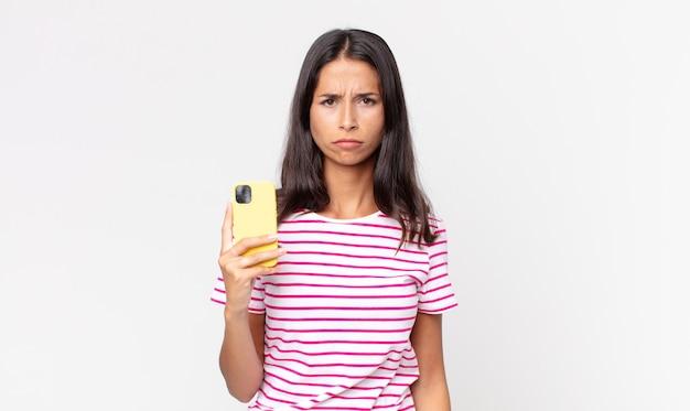 Молодая латиноамериканская женщина грустит, расстроена или злится, смотрит в сторону и держит смартфон