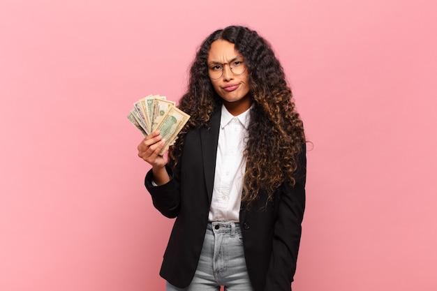 Молодая латиноамериканка грустит, расстроена или злится, смотрит в сторону с негативным отношением и хмурится в знак несогласия. доллар банкноты концепция