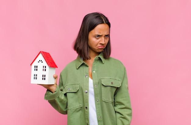 Молодая латиноамериканка грустит, расстроена или злится, смотрит в сторону с негативным отношением и хмурится в знак несогласия