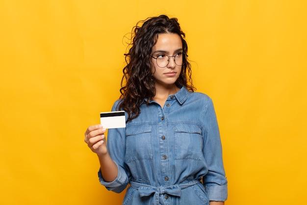 젊은 히스패닉계 여성이 슬프거나 화를 내거나 분노를 느끼고 부정적인 태도로 측면을 바라보고 의견이 일치하지 않습니다.