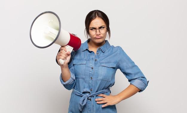 若いヒスパニック系女性は、悲しみ、動揺、または怒りを感じ、否定的な態度で横を向いて、意見の相違に眉をひそめています
