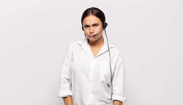 若いヒスパニック系の女性は、悲しみ、動揺、または怒りを感じ、否定的な態度で横を向いて、意見の相違に眉をひそめています