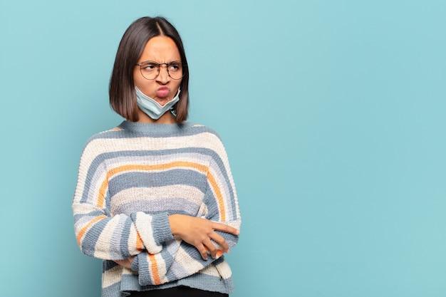 Молодая латиноамериканка грустит, расстроена или злится, смотрит в сторону с негативным отношением и хмурится в знак несогласия.