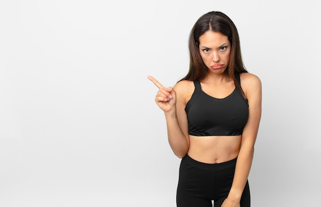 Young hispanic woman feeling sad and whiney with an unhappy look and crying. fitness concept
