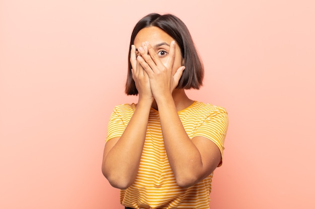 Young hispanic woman feeling scared or embarrassed, peeking or spying with eyes half-covered with hands