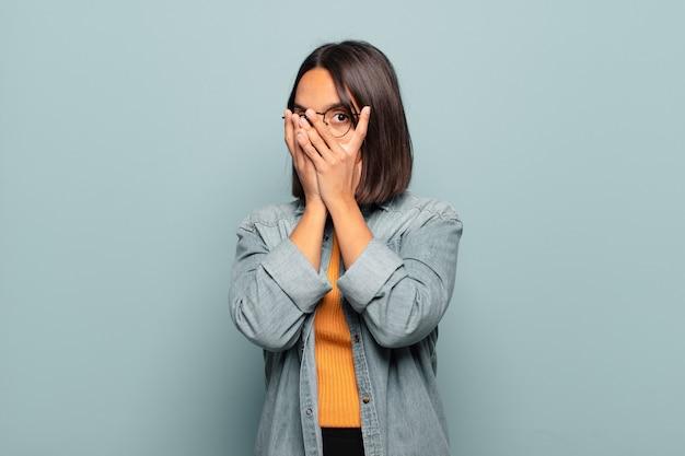 Молодая латиноамериканская женщина чувствует себя напуганной или смущенной, подглядывает или шпионит с полуприкрытыми руками глазами