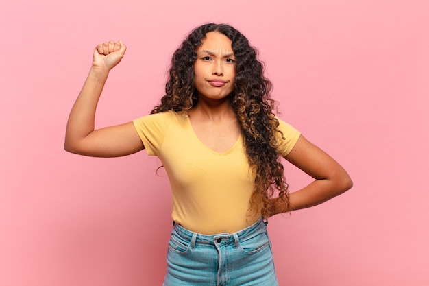 Young hispanic woman feeling serious, strong and rebellious, raising fist up, protesting or fighting for revolution
