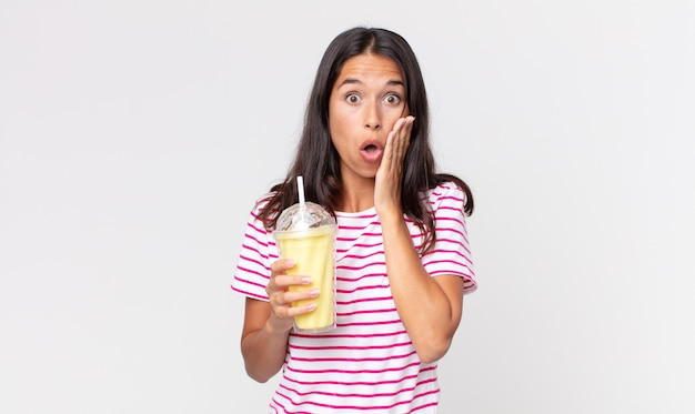 ショックと恐怖を感じ、バニラスムージーミルクセーキを保持している若いヒスパニック系女性