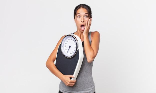 충격과 공포를 느끼고 체중계를 들고 있는 젊은 히스패닉 여성. 다이어트 개념