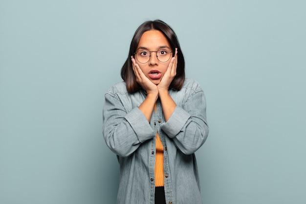 ショックを受けて怖がっている若いヒスパニック系の女性は、口を開けて頬に手を当てて恐怖を感じています