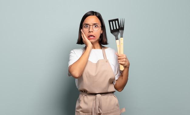 ヒスパニック系の若い女性は、ショックを受けて怖がり、口を開けて頬に手を当てて恐怖を感じています。