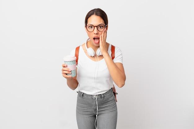 Молодая латиноамериканская женщина шокирована и напугана. студенческая концепция