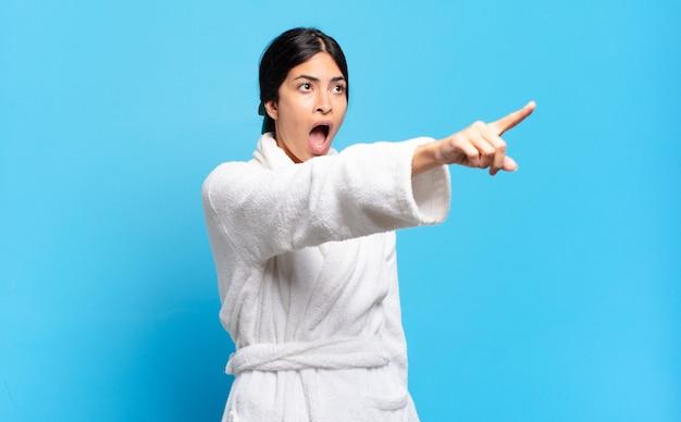 ショックを受けて驚いた若いヒスパニック系女性は、驚いた口を開けた表情で畏敬の念を抱いて上向きに指さし、見上げました。バスローブのコンセプト