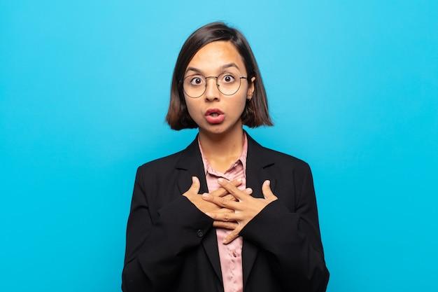 若いヒスパニック系の女性は、ショックを受けて驚いた、笑顔、心に手を差し伸べる、一人になって幸せ、または感謝の気持ちを示しています
