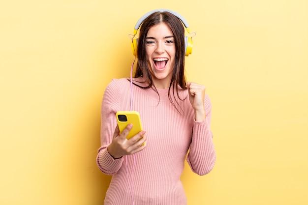 ショックを受け、笑い、成功を祝う若いヒスパニック系女性。ヘッドフォンと電話のコンセプト