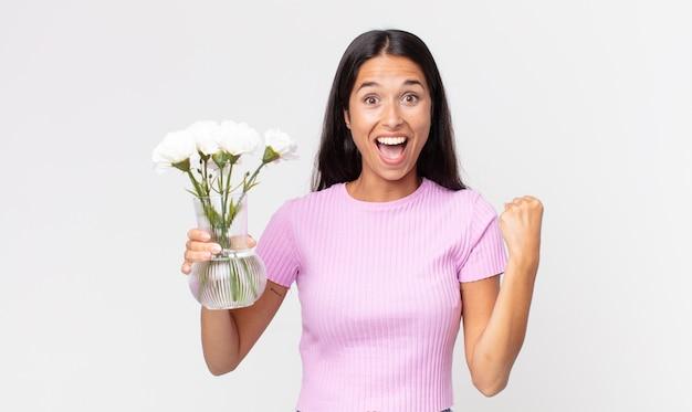 젊은 히스패닉 여성은 충격을 받고 웃고 장식용 꽃을 들고 성공을 축하합니다