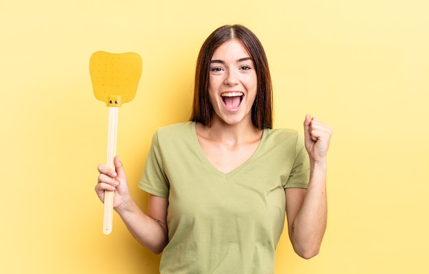 若いヒスパニック系女性はショックを受け、笑い、成功を祝っています。ハエを殺すコンセプト