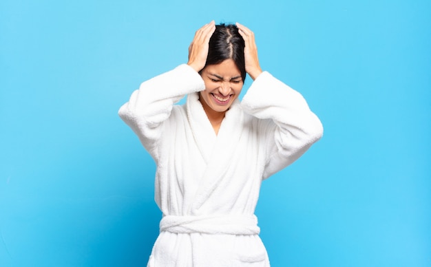 젊은 히스패닉 여성은 스트레스와 좌절감을 느끼며 손을 머리 위로 들고 피곤하고 불행하며 편두통을 앓고 있습니다. 목욕 가운 개념