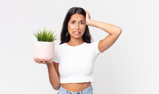 Молодая латиноамериканская женщина чувствует стресс, тревогу или страх, с руками за голову и с декоративным комнатным растением