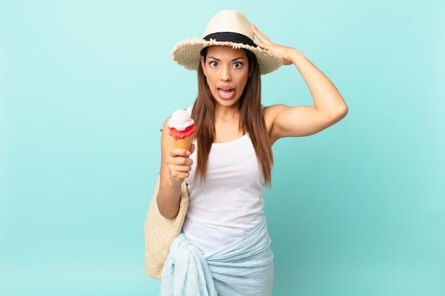 젊은 히스패닉계 여성은 머리에 손을 얹고 아이스크림을 들고 스트레스를 받고 불안해하거나 무서워합니다. 여름 개념